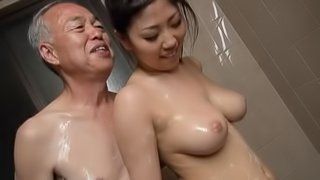 Stunning Asian chick with big tits sucking an old man's cock